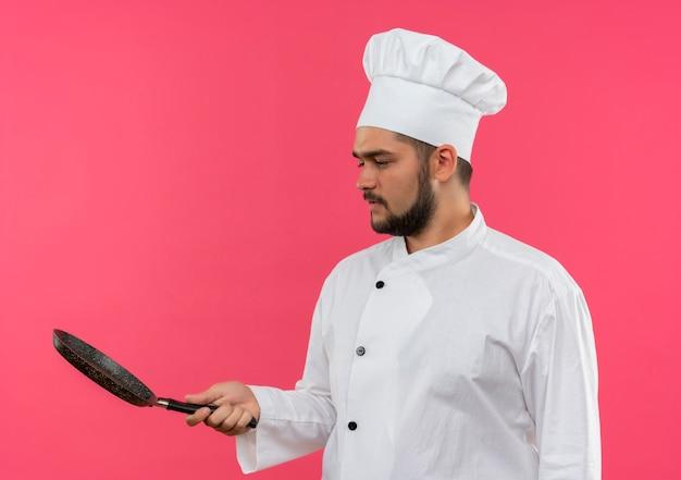 Jovem cozinheiro com uniforme de chef segurando e olhando para uma frigideira isolada no espaço rosa