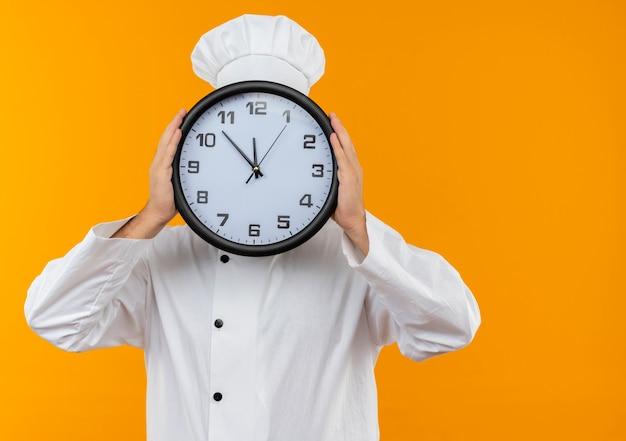 Jovem cozinheiro com uniforme de chef segurando e se escondendo atrás de um relógio isolado no espaço laranja