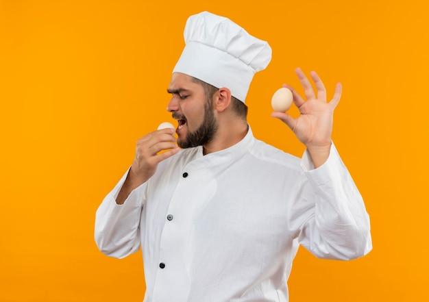 Jovem cozinheiro com uniforme de chef segurando e tentando morder um ovo isolado em um espaço laranja