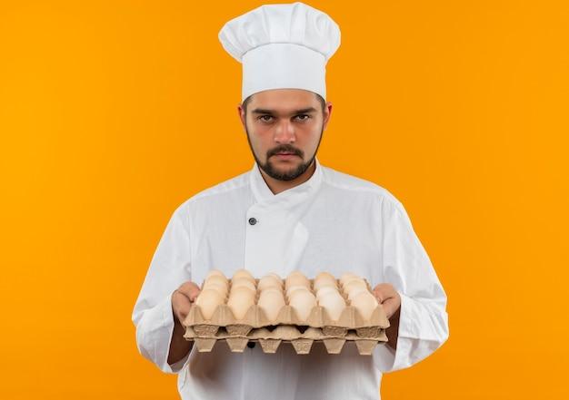 Jovem cozinheiro com uniforme de chef segurando uma caixa de ovos e parecendo isolado em um espaço laranja