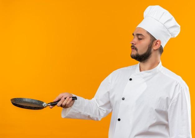 Jovem cozinheiro com uniforme de chef segurando uma frigideira com os olhos fechados, isolado em um espaço laranja