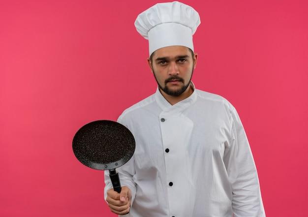 Jovem cozinheiro com uniforme de chef segurando uma frigideira, parecendo isolado no espaço rosa