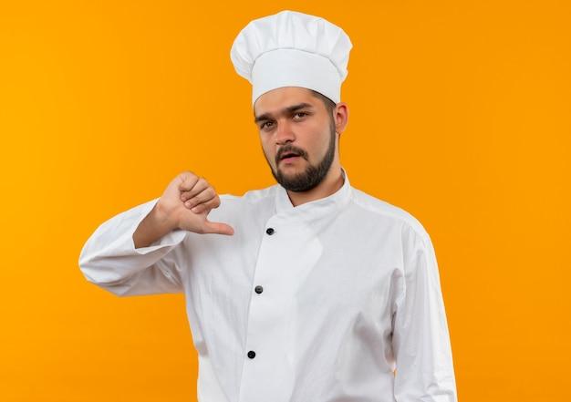 Jovem cozinheiro confiante com uniforme de chef apontando para si mesmo isolado na parede laranja