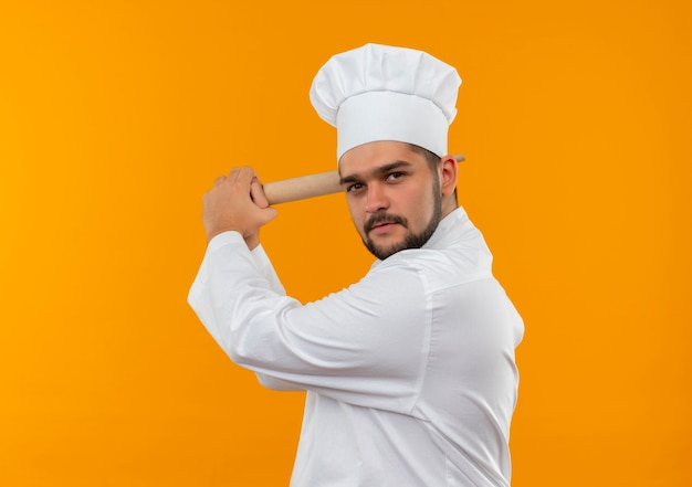 Jovem cozinheiro confiante com uniforme de chef em pé na vista de perfil, segurando o rolo de massa e se preparando para bater, isolado na parede laranja com espaço de cópia