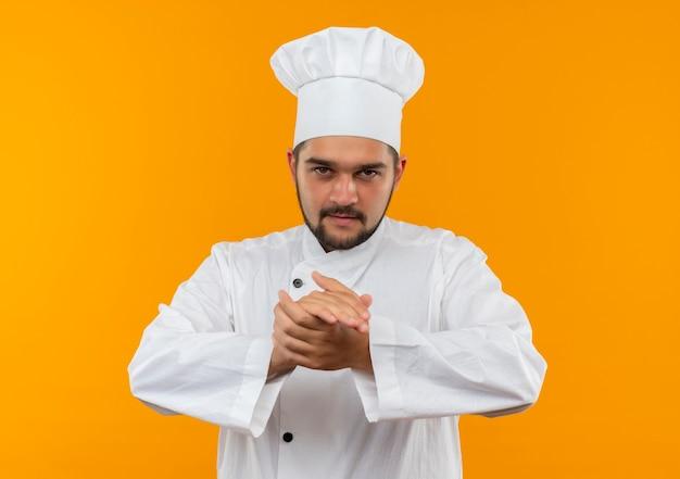 Jovem cozinheiro confiante com uniforme de chef, mantendo as mãos juntas isoladas na parede laranja