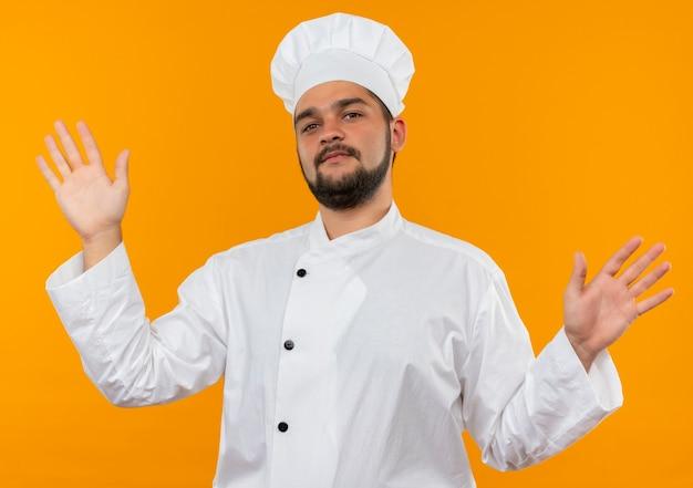 Jovem cozinheiro confiante com uniforme de chef, mostrando as mãos vazias, isoladas na parede laranja