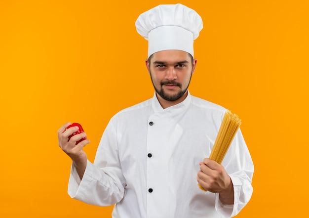 Jovem cozinheiro confiante com uniforme de chef segurando pimenta e macarrão espaguete isolado na parede laranja