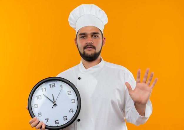 Jovem cozinheiro confiante em uniforme de chef segurando o relógio e mostrando a mão vazia, isolada na parede laranja
