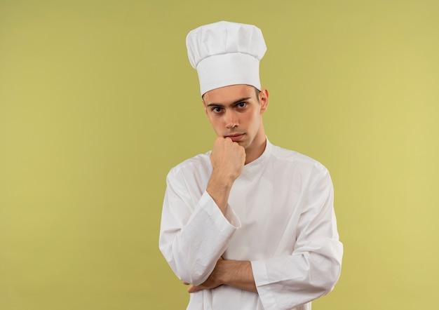 Jovem cozinheiro confiante vestindo uniforme de chef, colocando a mão sob o queixo na parede verde isolada com espaço de cópia