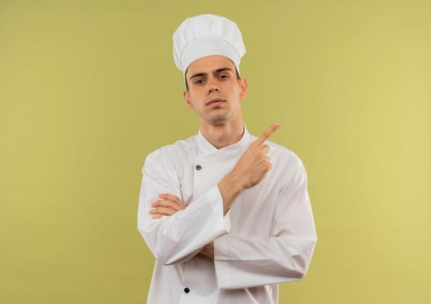 Jovem cozinheiro confiante vestindo uniforme de chef cruzando as mãos e apontando o dedo para o lado na parede verde isolada com espaço de cópia
