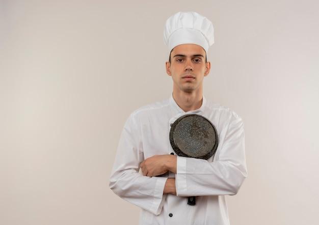 Jovem cozinheiro confiante vestindo uniforme de chef, cruzando as mãos e segurando uma frigideira na parede branca isolada com espaço de cópia