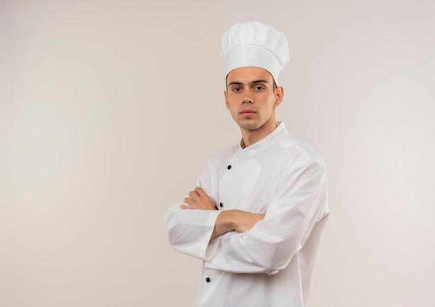 Jovem cozinheiro confiante vestindo uniforme de chef cruzando as mãos na parede branca isolada com espaço de cópia