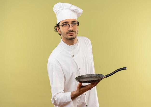 Jovem cozinheiro confiante vestindo uniforme de chef e óculos segurando uma frigideira sobre fundo verde