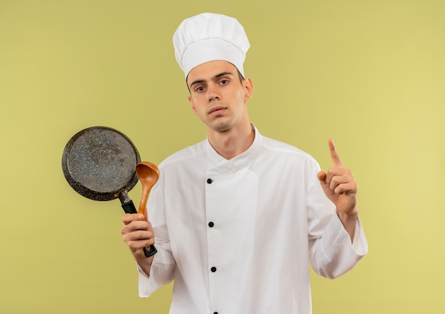 Jovem cozinheiro confiante vestindo uniforme de chef segurando uma frigideira e uma colher, mostrando seu gesto na parede verde isolada
