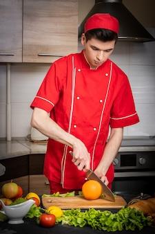 Jovem cozinheiro corta frutas e vegetais em fundo claro