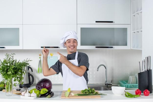Jovem cozinheiro de uniforme apontando para o armário da cozinha de frente