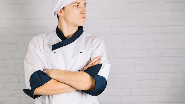 Jovem, cozinheiro, em, branca, cruzar braços, peito