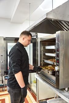 Jovem cozinheiro em uma túnica preta prepara lanches de catering