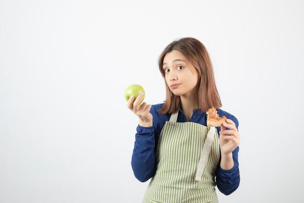Jovem cozinheiro escolhendo o que comer pizza e maçã verde.