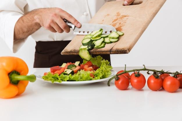 Jovem cozinheiro homem uniformizado cortando salada de legumes na placa de madeira isolada na parede branca