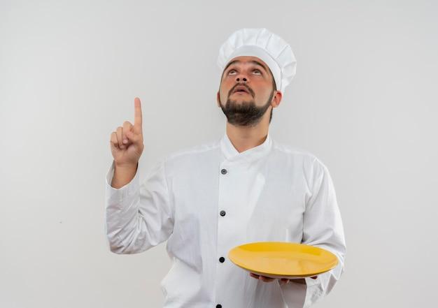 Jovem cozinheiro impressionado com uniforme de chef segurando o prato vazio, olhando e apontando para cima, isolado na parede branca