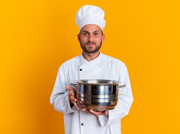 Jovem cozinheiro masculino caucasiano satisfeito com uniforme de chef e boné segurando a panela