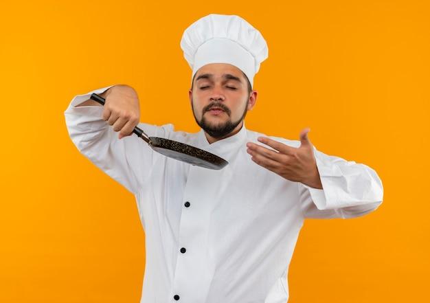 Jovem cozinheiro masculino com uniforme de chef segurando a frigideira e cheirando com os olhos fechados e a mão no ar isolado no espaço laranja