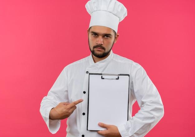 Jovem cozinheiro masculino com uniforme de chef segurando e apontando para a área de transferência e parecendo isolado no espaço rosa