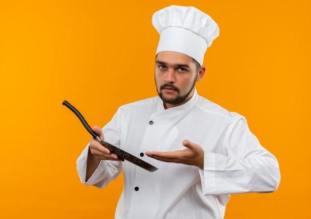 Jovem cozinheiro masculino com uniforme de chef segurando e apontando para a frigideira isolada no espaço laranja