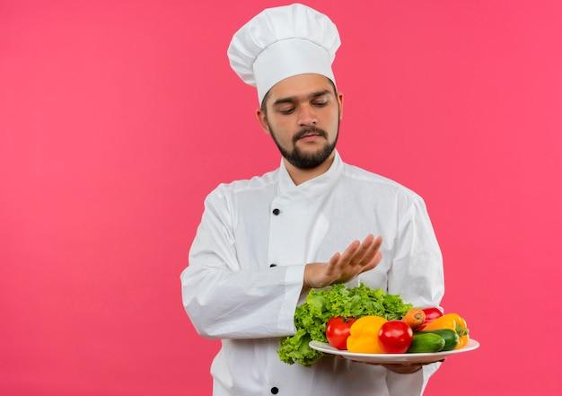 Jovem cozinheiro masculino em uniforme de chef segurando e olhando para o prato de legumes e mantendo a mão acima do prato isolado no espaço rosa