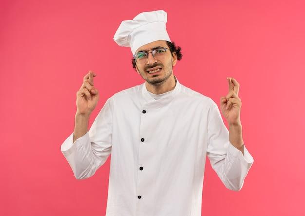 Jovem cozinheiro preocupado vestindo uniforme de chef e óculos cruzando os dedos