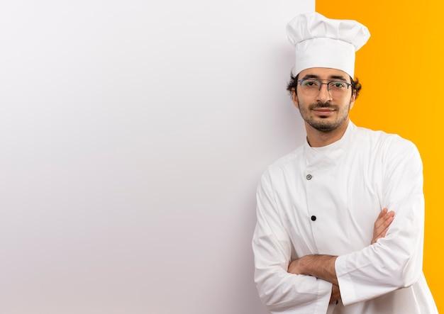 Jovem cozinheiro satisfeito vestindo uniforme de chef e óculos, cruzando as mãos em pé na parede branca isolada na parede amarela com espaço de cópia