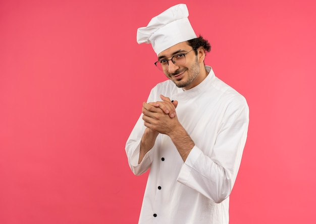Jovem cozinheiro satisfeito vestindo uniforme de chef e óculos mostrando apertos de mão isolados na parede rosa