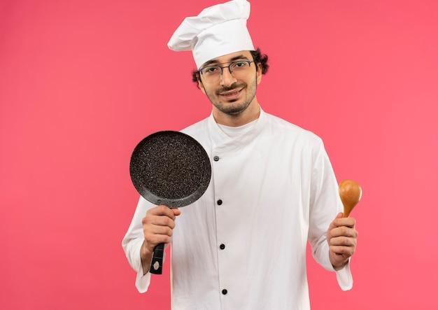 Jovem cozinheiro satisfeito vestindo uniforme de chef e óculos segurando uma frigideira e uma colher