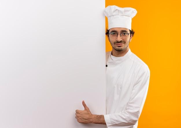 Jovem cozinheiro satisfeito vestindo uniforme de chef e óculos segurando uma parede branca com o polegar isolado na parede amarela com espaço de cópia