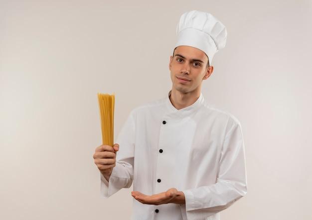 Jovem cozinheiro satisfeito vestindo uniforme de chef, mostrando espaguete na mão com espaço de cópia