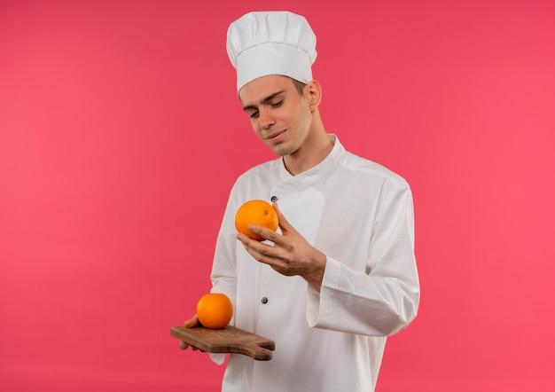 Jovem cozinheiro satisfeito vestindo uniforme de chef segurando e olhando laranja na tábua com espaço de cópia