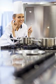 Jovem cozinheiro sorridente que mostra o sinal ok