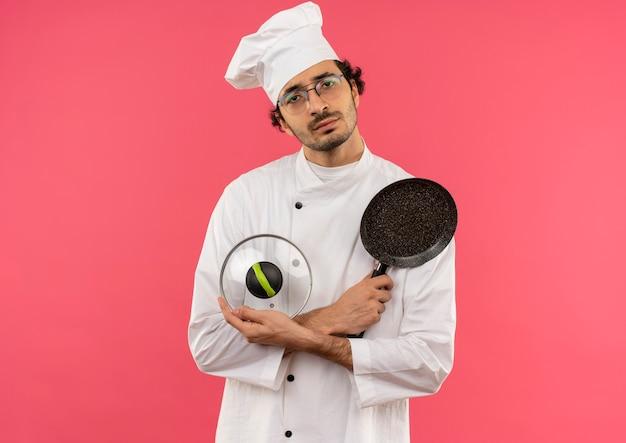 Jovem cozinheiro vestindo uniforme de chef e óculos segurando e cruzando a frigideira com tampa