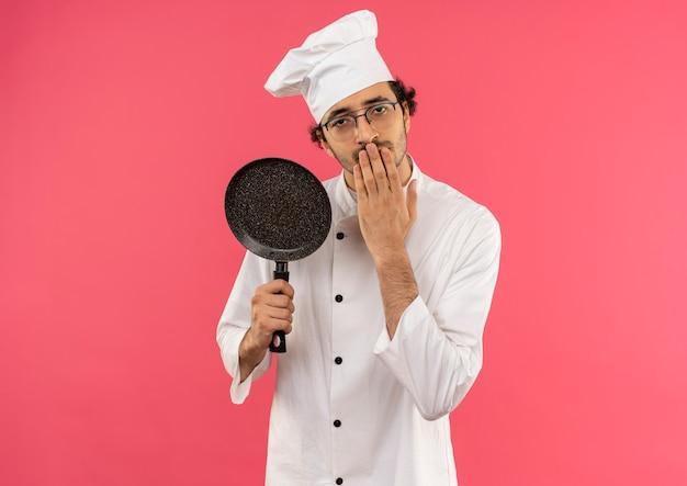 Jovem cozinheiro vestindo uniforme de chef e óculos segurando uma frigideira e tapando a boca