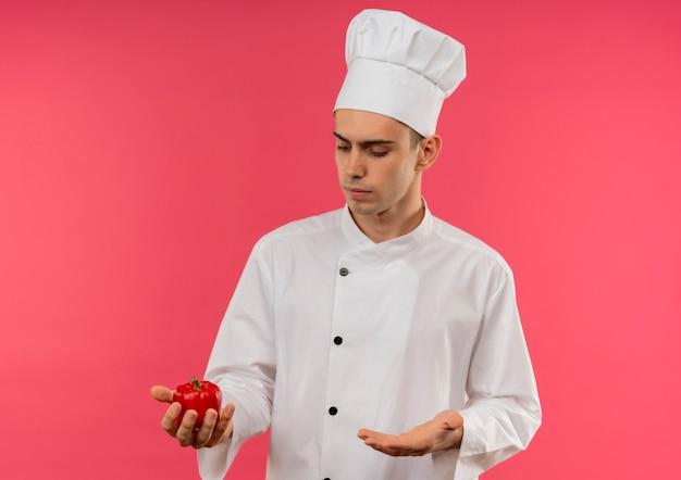 Jovem cozinheiro vestindo uniforme de chef segurando e olhando para papper