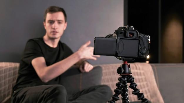 Jovem criador de conteúdo falando e gesticulando homem filmando a si mesmo usando uma câmera em um tripé