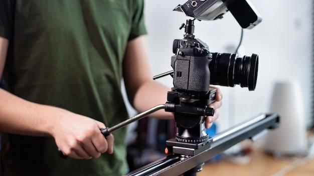 Jovem criador de conteúdo filmando com a câmera no controle deslizante, equipamento profissional