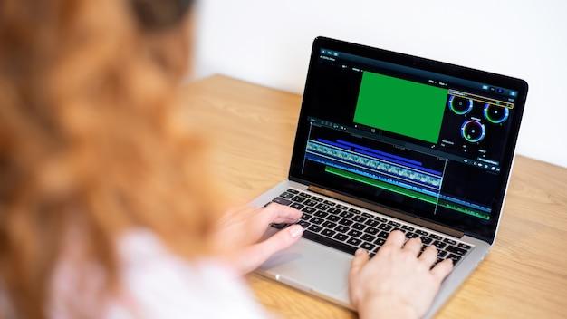 Jovem criadora de conteúdo editando vídeo em seu laptop. trabalhando em casa