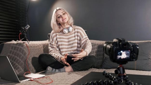 Jovem criadora de conteúdo loira falando, filmando a si mesma usando uma câmera em um tripé enquanto grava