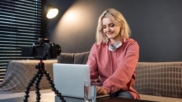 Jovem criadora de conteúdo sorridente loira com fones de ouvido trabalhando em seu laptop na mesa com a câmera
