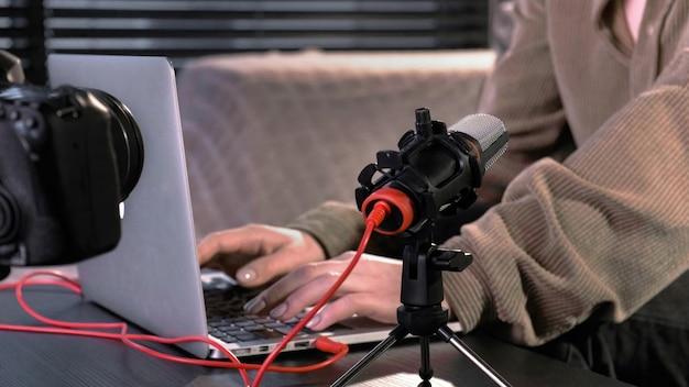 Jovem criadora de conteúdo trabalhando em seu laptop na mesa com a câmera em um tripé, microfone