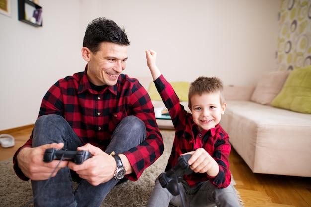 Jovem criança do sexo masculino alegre está comemorando a vitória em jogos de console, mantendo o punho acima da cabeça, enquanto seu pai orgulhosamente está sorrindo para ele enquanto está sentado no chão.