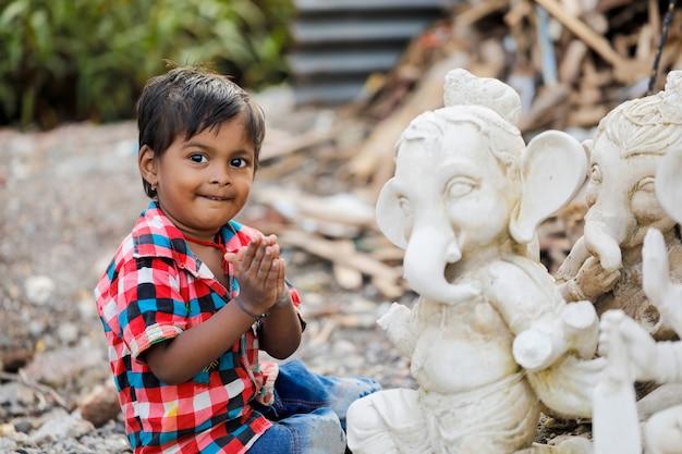 Jovem criança indiana com senhor ganesha