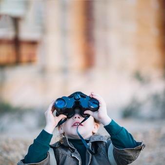Jovem criança olhando através de binóculos